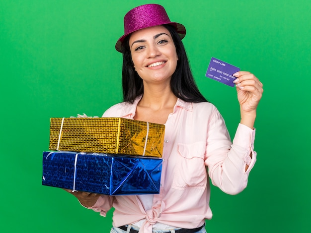 Smiling young beautiful girl wearing party hat holding gift boxes with credit card isolated on green wall