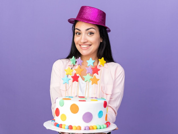 카메라에 케이크를 들고 파티 모자를 쓰고 웃는 젊은 아름 다운 소녀