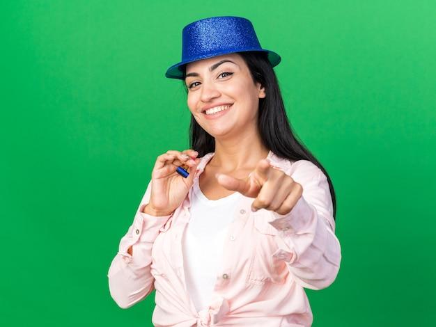 당신에게 몸짓을 보여주는 파티 휘파람을 들고 파티 모자를 쓰고 웃는 젊은 아름 다운 소녀