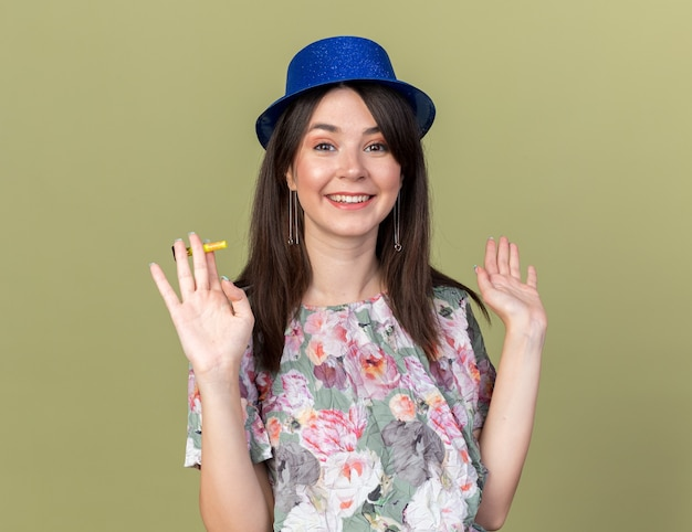 オリーブグリーンの壁に分離された手を広げてパーティーの笛を保持しているパーティー帽子をかぶって笑顔の若い美しい少女