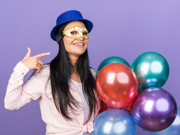 Smiling young beautiful girl wearing party hat and masquerade eye mask holding balloons points at herself isolated on blue wall