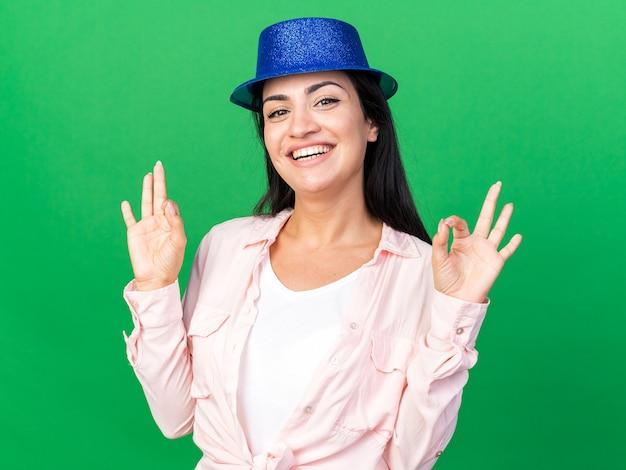 Sorridente giovane bella ragazza che indossa un cappello da festa che mostra gesto ok