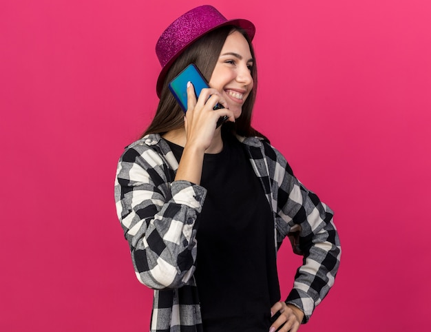 Smiling young beautiful girl wearing party hat speaks on phone putting hand on hip