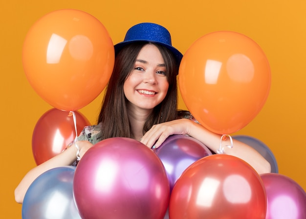 Smiling young beautiful girl wearing party hat standing behind balloons
