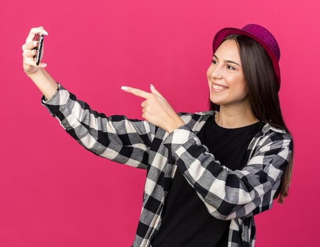파티 모자를 쓰고 웃고 있는 아름다운 소녀는 분홍색 벽에 격리된 전화기에서 셀카 포인트를 찍습니다.