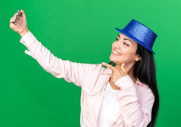 パーティーハットをかぶって笑顔の若い美しい女の子が電話で自分撮りポイントを取る