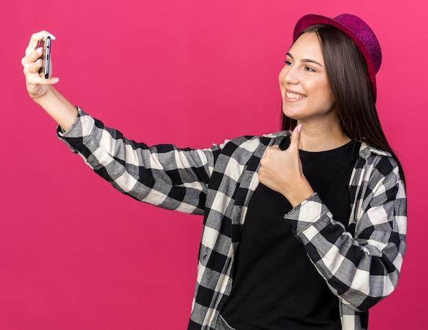 パーティーハットを身に着けている笑顔の若い美しい少女は、ピンクの壁に分離された親指を見せて自分撮りを取ります