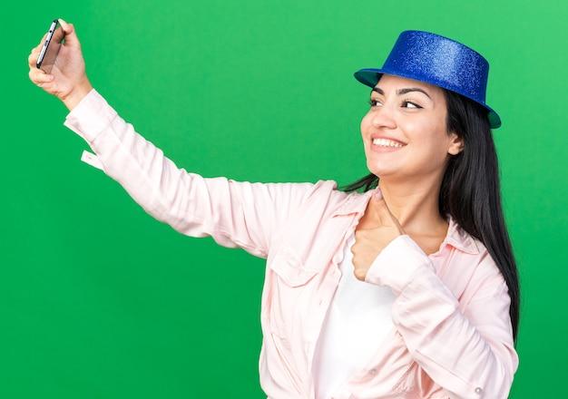 パーティーハットをかぶって笑顔の若い美しい女の子は親指を表示して自分撮りを取ります