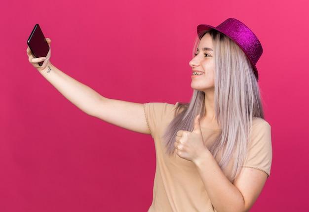 파티 모자를 쓰고 웃고 있는 아름다운 소녀가 엄지손가락을 보여주는 셀카를 찍습니다.