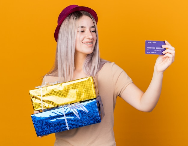 Smiling young beautiful girl wearing party hat with braces holding gift boxes and looking at credit card in her hand isolated on orange wall