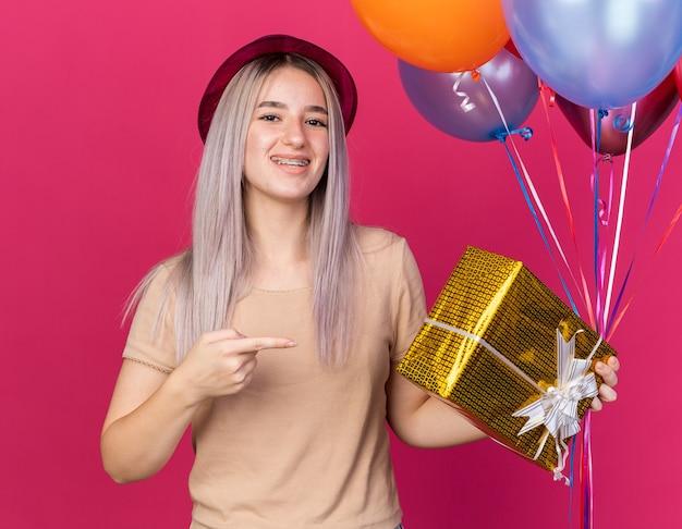 Sorridente giovane bella ragazza che indossa un cappello da festa con apparecchi ortodontici che tengono palloncini con scatola regalo