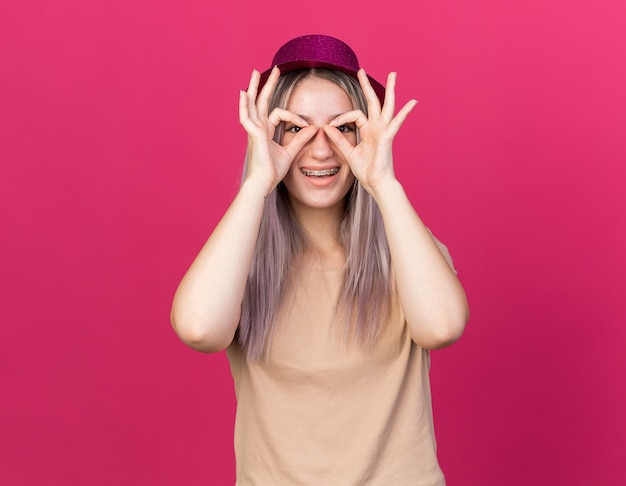 Smiling young beautiful girl wearing party hat with dental braces showing look gesture isolated on pink wall