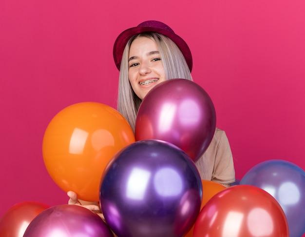 Sorridente giovane bella ragazza che indossa un cappello da festa con apparecchi dentali in piedi dietro palloncini