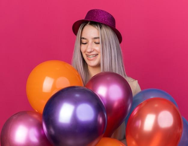 분홍색 벽에 격리된 풍선 뒤에 서 있는 치과 교정기가 달린 파티 모자를 쓰고 웃고 있는 아름다운 소녀