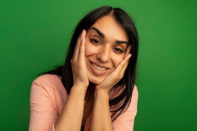 녹색 벽에 고립 된 뺨에 손을 댔을 분홍색 티셔츠를 입고 웃는 젊은 아름다운 소녀