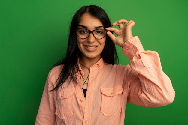 Улыбающаяся молодая красивая девушка в розовой футболке в очках, изолированных на зеленой стене