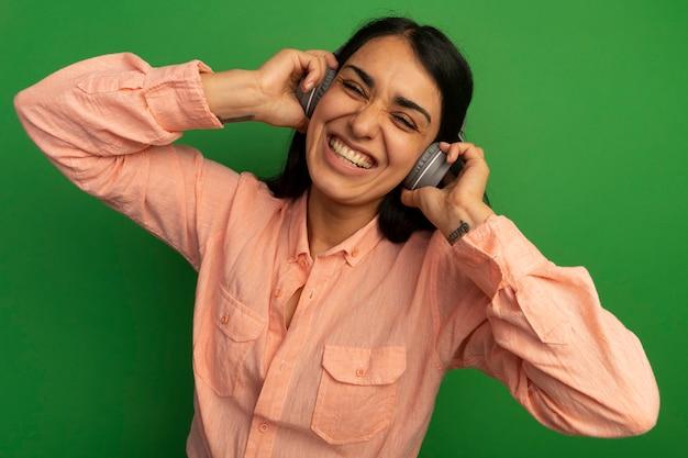 Улыбающаяся молодая красивая девушка в розовой футболке с наушниками изолирована на зеленой стене
