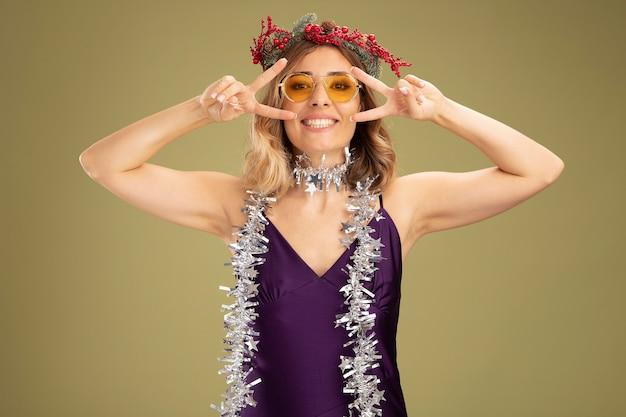 Улыбающаяся молодая красивая девушка в фиолетовом платье и очках с венком и гирляндой на шее, демонстрирующая жест мира на оливково-зеленом фоне
