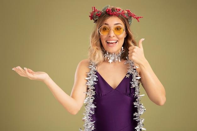 紫色のドレスとメガネを身に着けている笑顔の若い美しい少女の首に花輪と花輪がオリーブグリーンの背景で隔離の親指を示しています