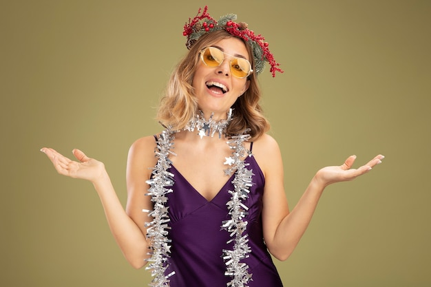 オリーブグリーンの背景で隔離の手を広げて首に花輪と花輪と紫色のドレスとメガネを身に着けている若い美しい少女の笑顔