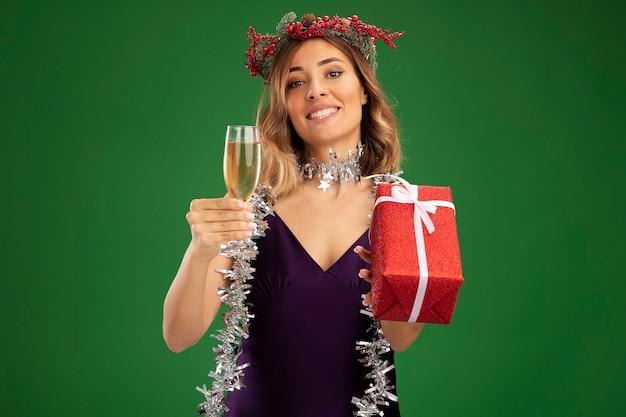 Улыбающаяся молодая красивая девушка в фиолетовом платье и венке с гирляндой на шее держит бокал шампанского с подарочной коробкой, изолированной на зеленом фоне