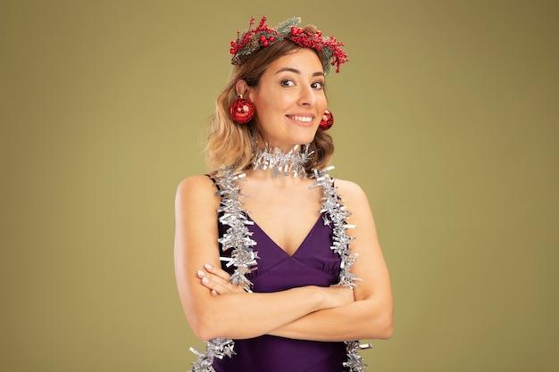 紫色のドレスと花輪を着て、オリーブグリーンの背景で隔離の手を交差する耳にクリスマスボールを保持している首に花輪と笑顔の若い美しい少女