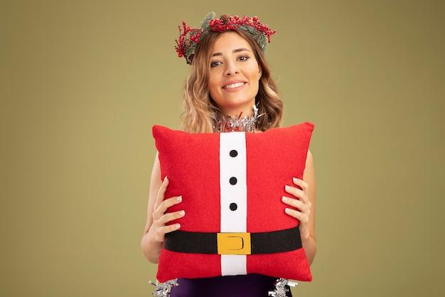 オリーブグリーンの背景で隔離のクリスマス枕を保持している首に花輪と紫色のドレスと花輪を身に着けている若い美しい少女の笑顔