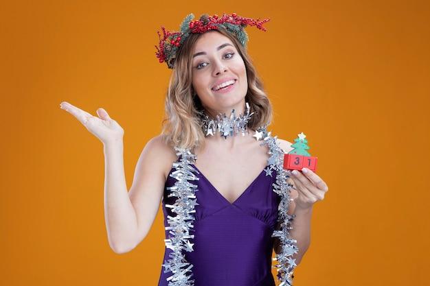 コピースペースと茶色の背景で隔離の側で手でクリスマスのおもちゃのポイントを保持している首に花輪と紫色のドレスと花輪を身に着けている若い美しい少女の笑顔