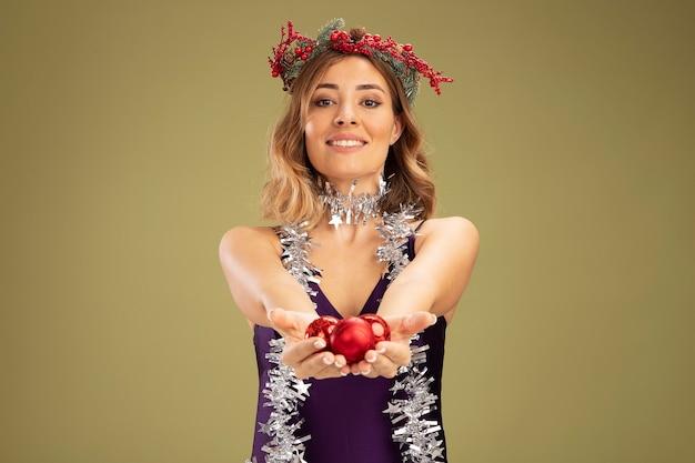 Улыбающаяся молодая красивая девушка в фиолетовом платье и венке с гирляндой на шее, протягивая елочные шары на камеру, изолированную на оливково-зеленом фоне