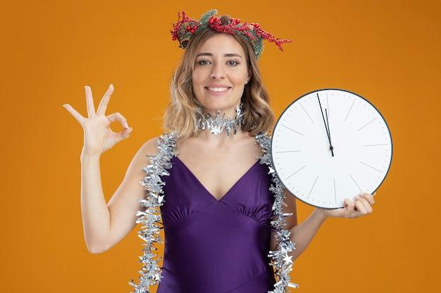 茶色の背景に分離された大丈夫なジェスチャーを示す壁時計を保持している首に花輪と紫色のドレスと花輪を身に着けている若い美しい少女の笑顔
