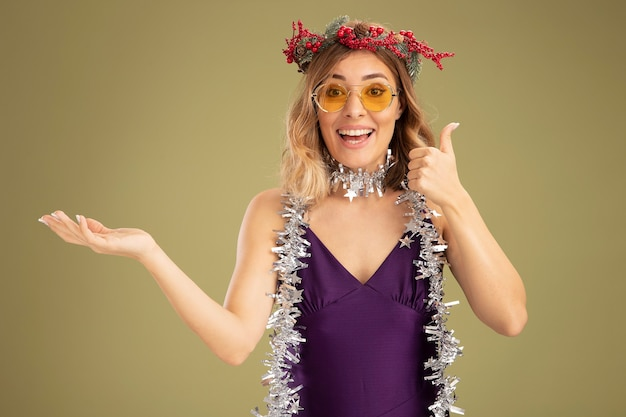 Smiling young beautiful girl wearing purple dress and glasses with wreath and garland on neck showing thumb up isolated on olive green background