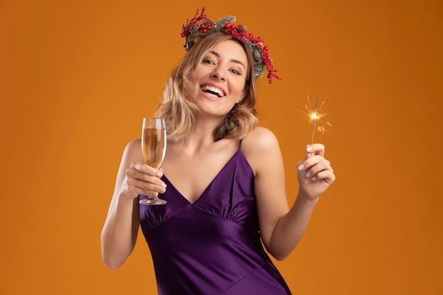 茶色の背景で隔離のシャンパングラスと線香花火を保持している花輪と紫色のドレスを着て笑顔の若い美しい少女