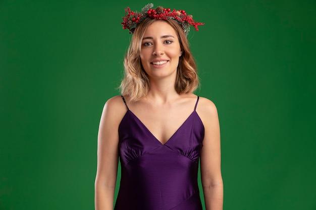 緑の背景に分離された花輪と紫色のドレスを着て笑顔の若い美しい少女