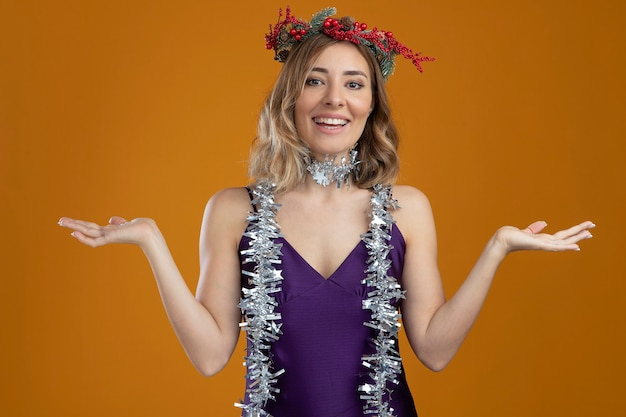 Smiling young beautiful girl wearing purple dress with wreath spreading hands isolated on brown background