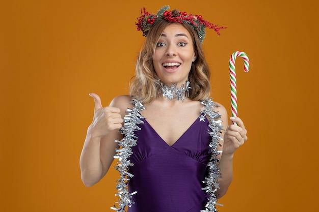 茶色の背景で隔離の親指を示すクリスマスキャンディーを保持している首に花輪と花輪と紫色のドレスを着て笑顔の若い美しい少女