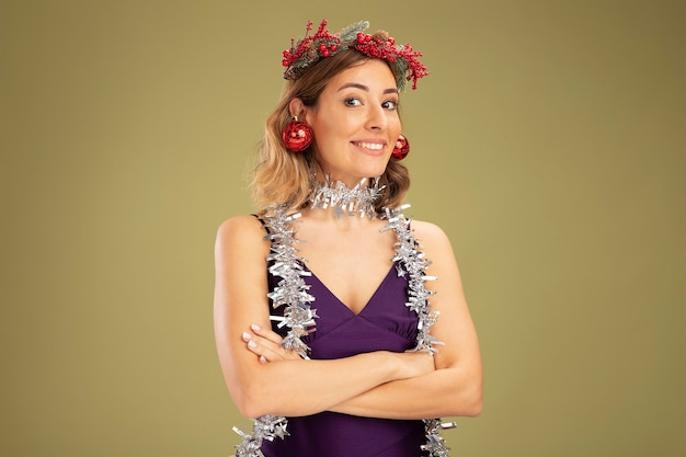 Smiling young beautiful girl wearing purple dress and wreath with garland on neck holding christmas balls on ears crossing hands isolated on olive green background