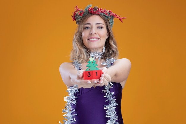 Smiling young beautiful girl wearing purple dress and wreath with garland on neck holding out christmas toy at camera isolated on brown background