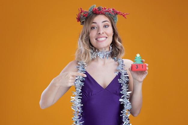 Sorridente giovane bella ragazza che indossa abito viola e ghirlanda con ghirlanda sul collo che tiene e indica il giocattolo di natale isolato su sfondo marrone