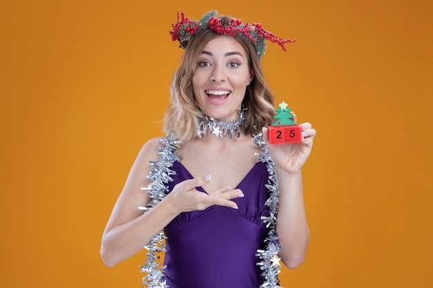 Sorridente giovane bella ragazza che indossa abito viola e corona con ghirlanda sulla tenuta del collo e punti al giocattolo di natale isolato sulla parete marrone