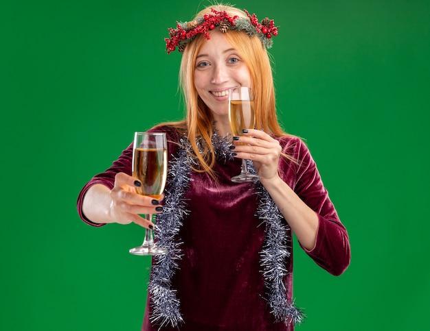 Giovane bella ragazza sorridente che porta vestito rosso con la corona e la ghirlanda sul collo che tiene fuori un bicchiere di champagne alla macchina fotografica isolata su fondo verde