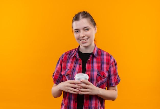 Улыбающаяся молодая красивая девушка в красной рубашке, держащая чашку кофе на изолированном желтом фоне с копией пространства
