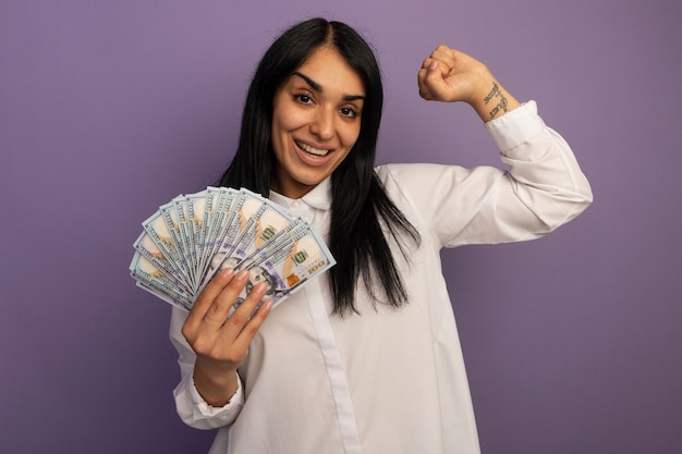 Smiling young beautiful girl wearing white t-shirt holding cash and showing yes gesture isolated on purple