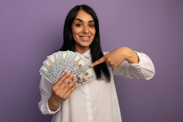 Smiling young beautiful girl wearing white t-shirt holding and points at cash isolated on purple