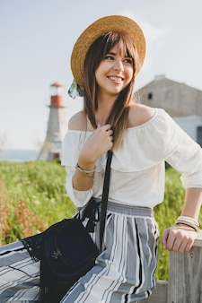 Smiling young beautiful stylish woman, spring summer fashion trend, boho style, straw hat, countryside weekend, sunny, black purse