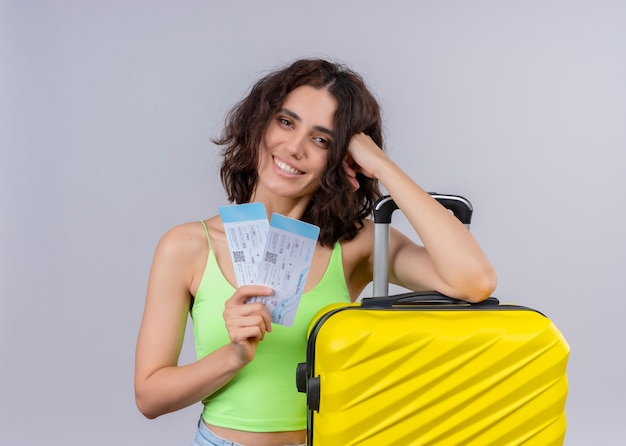 Smiling young beautiful traveler woman holding airplane tickets and suitcase on isolated white wall