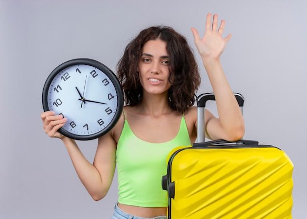 Smiling young beautiful traveler woman holding clock and suitcase and doing bye gesture on isolated white wall