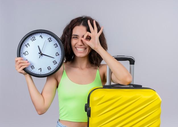 Sorridente giovane bella donna viaggiatore che tiene orologio e valigia e che fa gesto di sguardo sulla parete bianca isolata