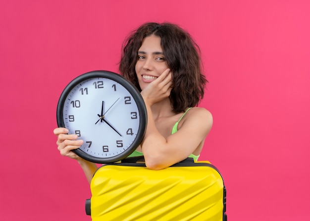 Smiling young beautiful traveler woman holding suitcase and clock on isolated pink wall