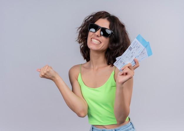 サングラスをかけていると飛行機のチケットを押しながら孤立した白い壁に拳を上げる若い美しい旅行者の女性の笑顔
