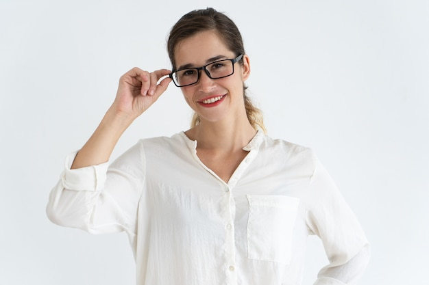 Smiling young beautiful woman adjusting glasses and looking at camera.